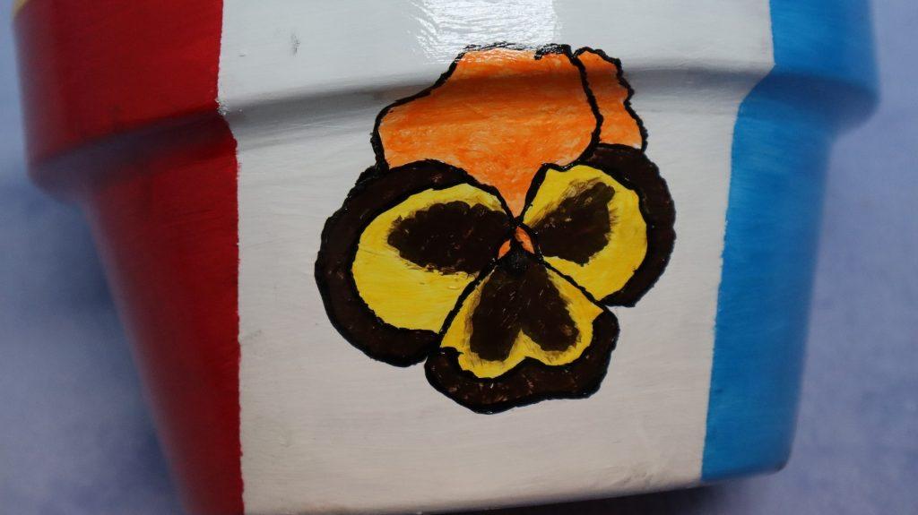 Dibujando flor de Pensamientos sobre maceta de arcilla cocida